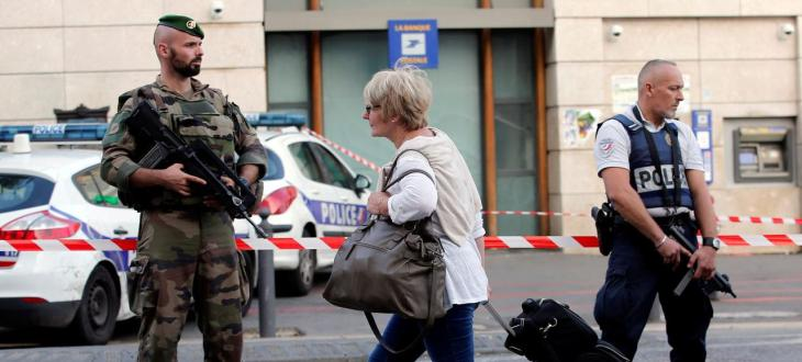 A traveller walks past a soldier and policeman who secure a street near the Saint-Charles train station after French soldiers shot and killed a man who stabbed two women to death at the main train station in Marseille